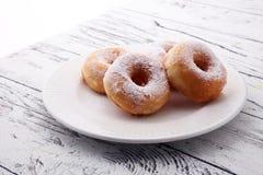 Напудренные donuts сахара на деревенской белой таблице Стоковое Изображение