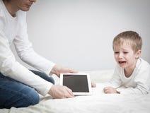 Наркомания компьютера, родитель принимая вне сенсорную панель от ребенка стоковое фото rf