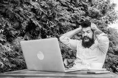 Наркоман компютерной игры Gamer участвуя в игре ПК сыгранной на ноутбуке Счастливый хипстер играя компютерную игру летом стоковые фотографии rf