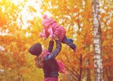 нарруfamilj. Mamman och behandla som ett barn dottern för går i höst Arkivbild