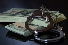 Наручники и деньги в темноте стоковая фотография