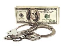 Наручники и доллары полиции на белой предпосылке Стоковые Изображения