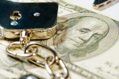 Наручники на куче долларовых банкнот Стоковые Фотографии RF