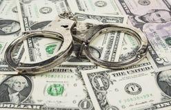 Наручники одна банкнота доллара в кренах на белой предпосылке стоковое изображение