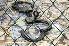 Наручники с ключом на предпосылке долларов под плетением провода (решетка) стоковые фото