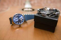 Наручные часы, браслет и акустическая гитара на заднем плане Стоковое Изображение RF