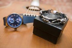 Наручные часы, браслет и акустическая гитара на заднем плане Стоковое фото RF