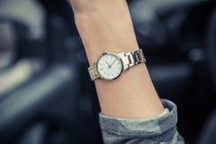 Наручные часы женщин на руке девушки Дозор золота женщин E стоковые фотографии rf
