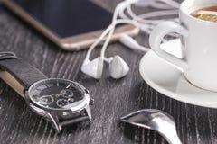Наручные часы и мобильный телефон с наушниками и чашкой кофе на темном деревянном столе стоковые фото