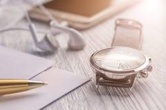 Наручные часы, мобильный телефон с наушниками и почта дела с ручкой на старом белом рабочем столе офиса стоковые изображения