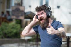 Насладитесь свободными песнями ежедневными Хипстер человека бородатый с музыкой наушников слушая Хипстер наслаждается высококачес стоковое изображение