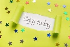 Насладитесь сегодня фразой показывая вверх под сорванной желтой бумагой Стоковое Изображение