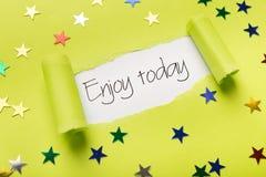 Насладитесь сегодня фразой показывая вверх под сорванной желтой бумагой Стоковые Изображения