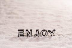 Насладитесь словом на белом песке стоковое изображение