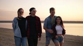 Наслаждаться жизнью с лучшими другами 2 красивых молодых пары идя пляжем совместно в сумрак вечера Мальчики акции видеоматериалы