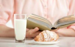 Наслаждаться расслабляющим моментом с книгой, круассаном и стеклом mil стоковое фото