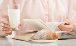 Наслаждаться расслабляющим моментом с книгой, круассаном и стеклом mil стоковое фото rf