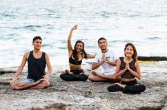 Наслаждаться свободным временем с друзьями Жизнерадостные молодые люди имея полезного время работы совместно на пляже стоковая фотография