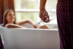Наслаждающся ванной с шампанским в стеклах - парой ослабляя совместно в ванне стоковое фото rf