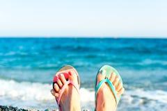 Наслаждение летнего времени! Ноги ` s дамы на пляже Океанские волны подпирают Стоковое Фото