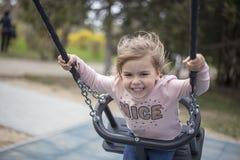 Наслаждение маленькой девочки от катания на качании стоковая фотография rf