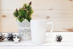 Насмешка рождества вверх ввела чашку в моду изображения продукта запаса белую, сцену рождества с белой пустой кружкой кофе котора стоковая фотография rf