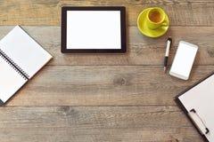 Насмешка стола офиса вверх по шаблону с таблеткой, умным телефоном, тетрадью и чашкой кофе Взгляд сверху с космосом экземпляра стоковое изображение rf