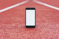 Насмешливый поднимающий вверх смартфон на стадионе для бега Концепция на теме спорта стоковая фотография rf