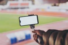 Насмешливый поднимающий вверх смартфон с ручкой selfie в руках человека на предпосылке стадиона Парень принимает selfie стоковая фотография rf