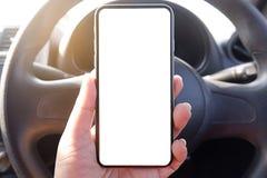 насмешливый поднимающий вверх телефон удерживания руки водителя в экране автомобиля пустом ясном для текста рекламирует фоновое и стоковая фотография