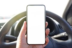 насмешливый поднимающий вверх телефон удерживания руки водителя в экране автомобиля пустом ясном для текста рекламирует фоновое и стоковые изображения