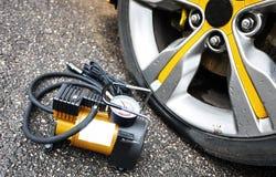 Насос автомобиля Автоматический компрессор автомобиля поможет вам нагнести воздух не только в колесах вашего автомобиля, но также стоковое фото rf
