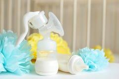 Насос груди и бутылки младенца с молоком, различным праздничным бумажным оформлением перед спальней младенца Оно ` s celebra дня  Стоковые Фотографии RF