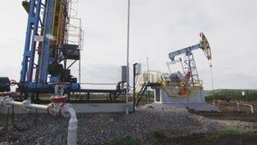 Насос Джек работает на нефтяной скважине против облачного неба акции видеоматериалы