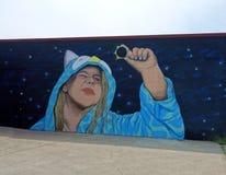 Настенная роспись девушки держа солнечное затмение Стоковые Изображения RF