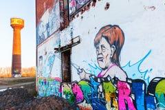 Настенная роспись немецкого федерального канцлера Ангелы Меркели на покинутой фабрике Стоковое фото RF