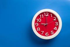 Настенные часы установленные на предпосылку цвета Концепция времени последняя Стоковое Изображение