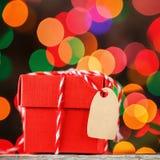 Настоящий момент или коробка красного цвета рождества для секретного santa с биркой для текста на красочной предпосылке bokeh кар Стоковая Фотография RF