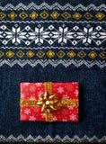 Настоящий момент обернутый красным цветом на свитере рождества Стоковые Фото