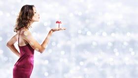 Настоящий момент подарка рождества, женщина с пакетом на запачканном ярком lig Стоковая Фотография