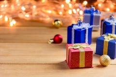 Настоящий момент подарочной коробки и украшает на деревянном столе Стоковая Фотография RF