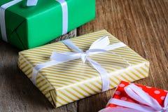 Настоящий момент подарочной коробки и украшает на деревянном столе Стоковые Изображения