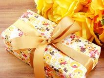 Настоящий момент подарочной коробки и предпосылка букета искусственных цветков желтеют тему Стоковое Изображение