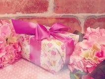 Настоящий момент подарочной коробки и предпосылка украшения цветков с винтажным цветом фильтра Стоковые Изображения RF