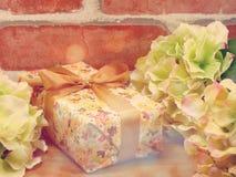 Настоящий момент подарочной коробки и предпосылка украшения цветков с винтажным цветом фильтра Стоковые Фото