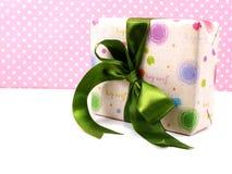 Настоящий момент подарочной коробки розовый с лентой на розовой предпосылке Стоковое Фото