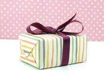 Настоящий момент подарочной коробки розовый с лентой на розовой предпосылке Стоковая Фотография