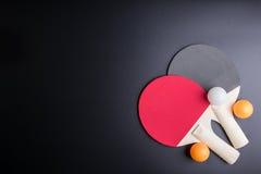 Настольный теннис ракетки с шариком пингпонга на черной предпосылке Spor Стоковые Изображения RF