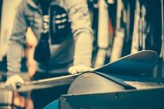 Настраивать и reapairs сноуборда Работник магазина зимы делая rep основания стоковые изображения rf