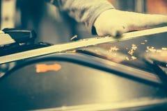 Настраивать и reapairs лыжи Работник магазина зимы делая низкопробный ремонт стоковая фотография